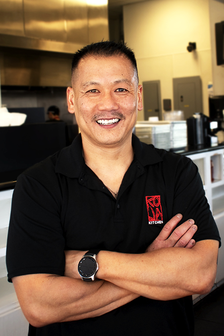 Image contains: Asian Male with a big smile and wearing KoJa Kitchen shirt with interior of a restaurant in background