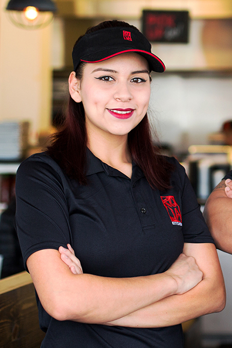 Image contains: Latina Female with a big smile and wearing KoJa Kitchen shirt with interior of a restaurant in background